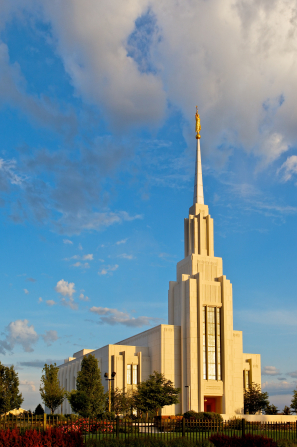 A full view of the Twin Falls Idaho Temple during the day, including the grounds with trees and flowers.
