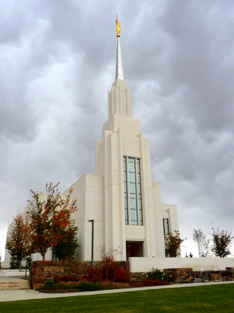 The Twin Falls Idaho Temple entrance, with a partial view of the grounds and with trees changing colors in autumn.