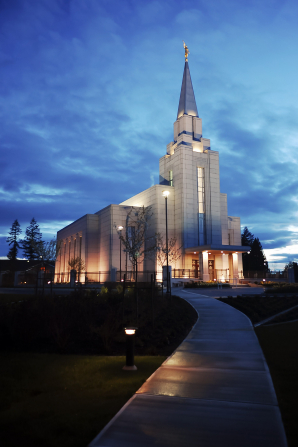 The walkway leading up to the front of the Vancouver British Columbia Temple, with a view of the entire temple lit up at night.
