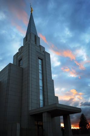 The front of the Vancouver British Columbia Temple after sunset, with a view of the entrance and the spire with the angel Moroni.
