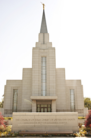 The front entrance to the Vancouver British Columbia Temple, with the name sign and a view of the angel Moroni on top of the spire.