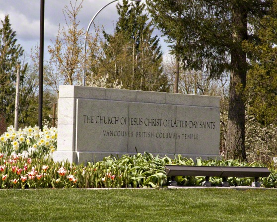 The Vancouver British Columbia Temple name sign, with tulips, daffodils, and trees around it.