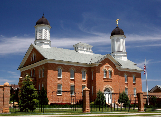 The whole Vernal Utah Temple, with a view of the entrance, both spires, and the fence surrounding the grounds.