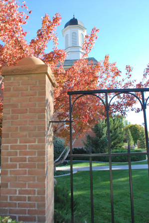 The gate to the grounds of the Vernal Utah Temple, with a view of a spire rising above the top of a tree.