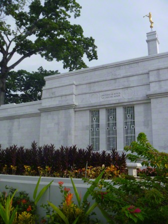 The side of the Villahermosa Mexico Temple, with a view of windows, the spire with the angel Moroni, and some flowers on the grounds.