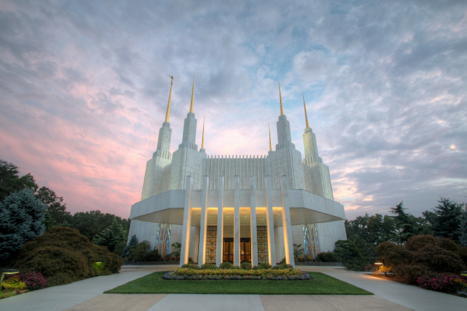 The entrance to the Washington D.C. Temple lit up, with a view of all six spires just after sunset.