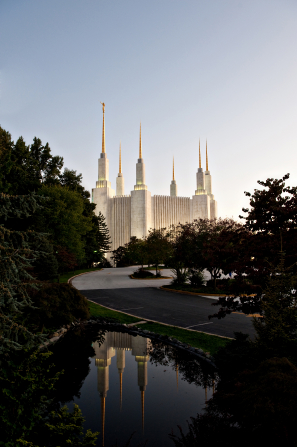 The entire Washington D.C. Temple lit up in the evening, with the reflecting pond in the foreground.