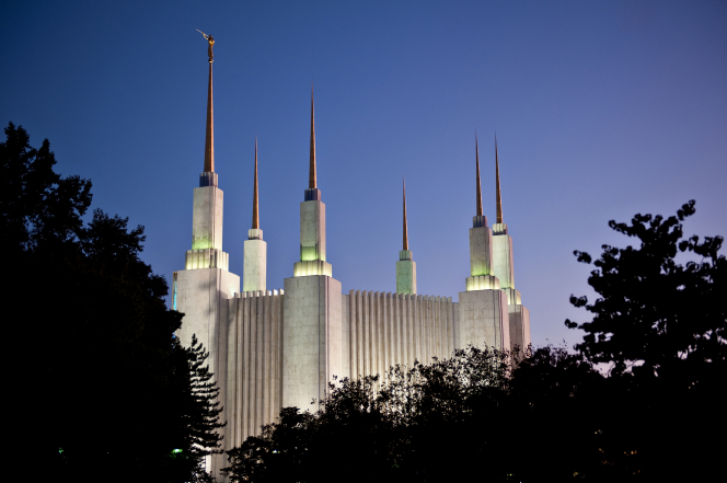All six spires of the Washington D.C. Temple lit up at night, above the tree line.