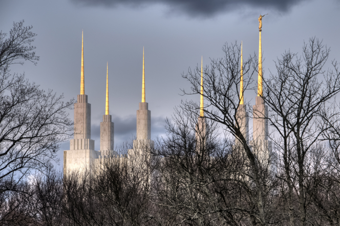 The six spires of the Washington D.C. Temple rise above the leafless tree line, with cloudy skies.