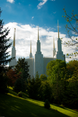 The Washington D.C. Temple, with all six spires in view, surrounded by high trees and grass.