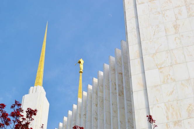 Two spires of the Washington D.C. Temple, with a partial view of the side and the angel Moroni on top.