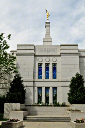 The stained-glass windows on the east side of the Winter Quarters Nebraska Temple, with tall bushes on either side and the spire with the angel Moroni on top.