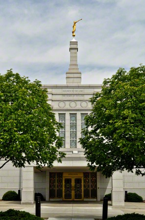 The front entrance to the Winter Quarters Nebraska Temple, with a view of the spire with the angel Moroni on top and two trees on either side of the temple.