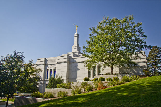 The east side of the Winter Quarters Nebraska Temple, including the grounds, with green-leafed trees and flowers.