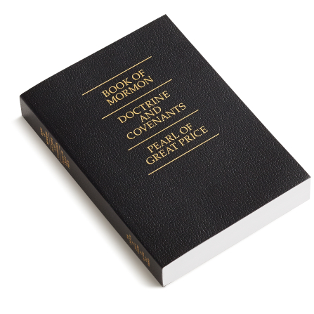 A photograph of a black softcover triple combination with gold text.