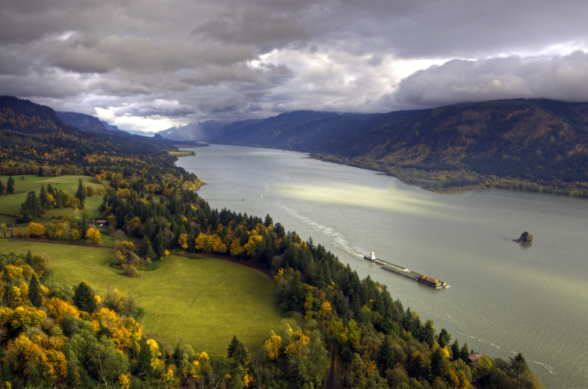 A barge floats down the Columbia River in autumn, with hills and trees on either side.