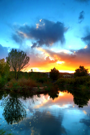 A sunset bursting through clouds and trees, reflected in a lake in St. George, Utah.