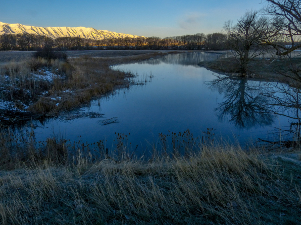 A river in Cache Valley in winter, with trees and mountains nearby.