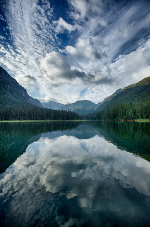 Clouds, mountains, and pine trees are reflected in a lake in Alaska.