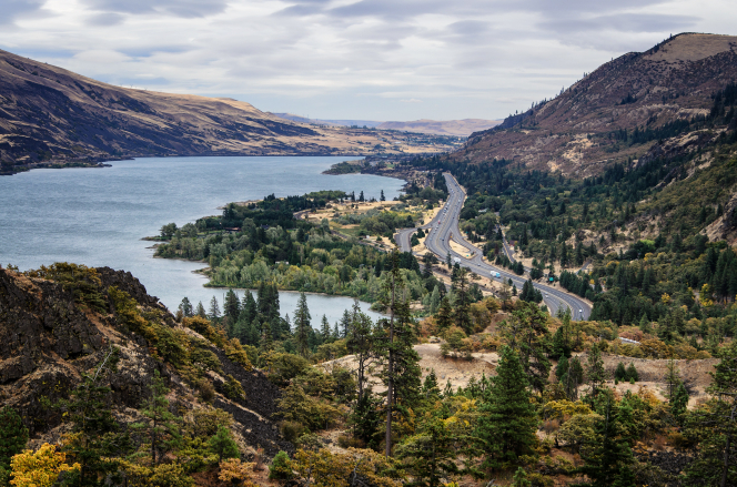 An aerial view of the Columbia River in Oregon, with a highway running alongside the river.