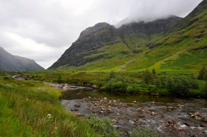 Fog lying low on mountains, with a stream running through a green, grassy valley in Scotland.