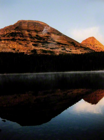 A red rock mountain is reflected in a lake with a clear, blue sky above.