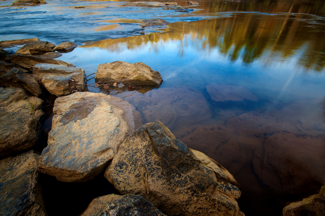 Rocks partially above the surface of a river, with the sky reflected in the water.