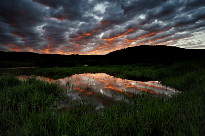 The sun rises through clouds over mountains and a pond surrounded by tall, green grass in Utah.