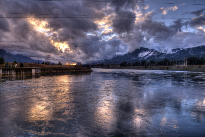 The sun sets over snow-tipped mountains and the frozen Columbia River in winter, with clouds in the sky.