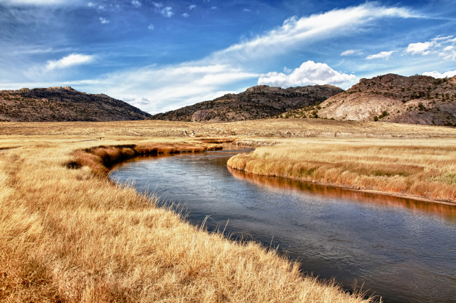 The Sweetwater River runs through a yellow, grassy meadow with hills in the background and clouds overhead.