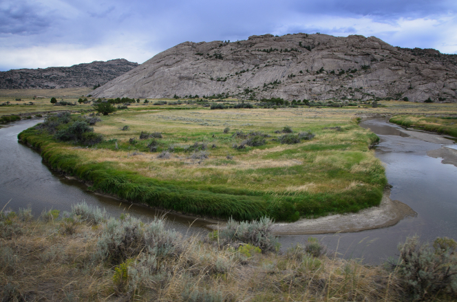 The Sweetwater River runs through Martin's Cove in Wyoming, with grass along the banks and mountains in the background.