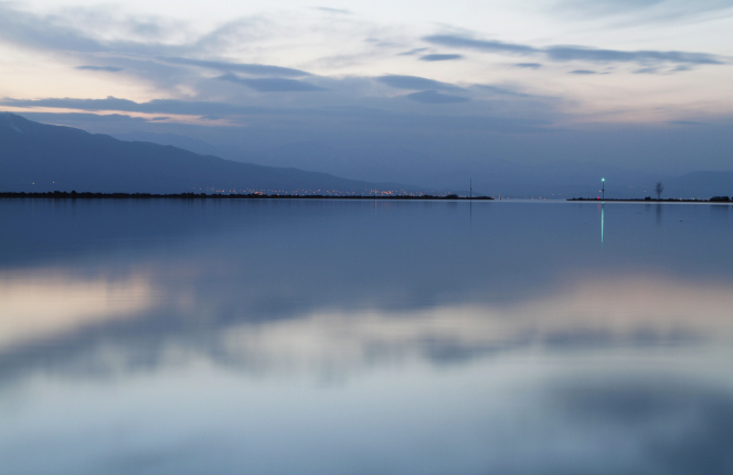 The sky reflected in Utah Lake, with a mountain and lights in the background.