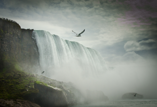 Three birds fly through mist over Niagara Falls, with clouds in the sky.