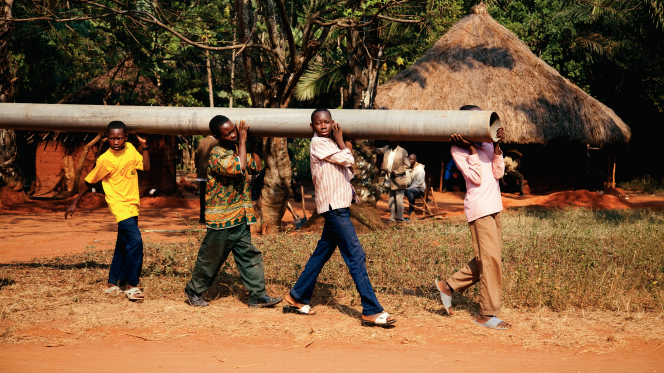 Four African boys walking in a line, carrying a long round pole on their shoulders and holding it in place with their hands.