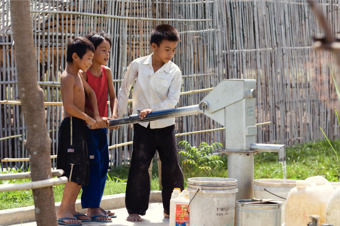 Three young boys in Cambodia standing and pumping clean water into a bucket from a metal hand-operated pump.