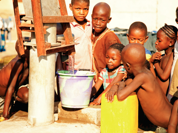 A group of African children standing closely by a tall water pump and watching clean water pour into a light purple bucket.