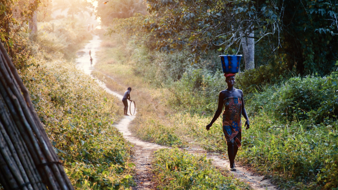 An African woman balancing a large bucket of water on her head while walking down a narrow path.