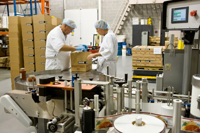 Two men in white aprons, blue gloves, and hairnets closing a box on a food packing line inside of Welfare Square.
