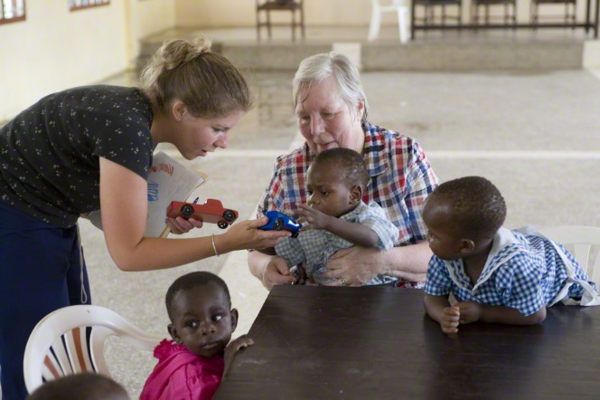 A woman in an orphanage holds an African child while another woman hands the child a wooden car, with two other children nearby.