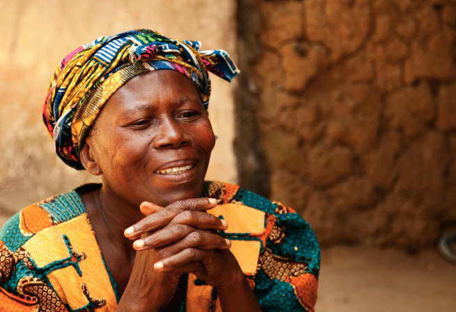 An African woman in a bright blue, yellow, and pink head wrap and shirt, with her chin resting on her two clasped hands.
