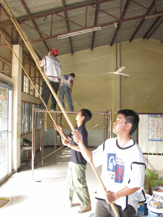 Four men in Mormon Helping Hands shirts painting with long poles inside a building in Thailand.