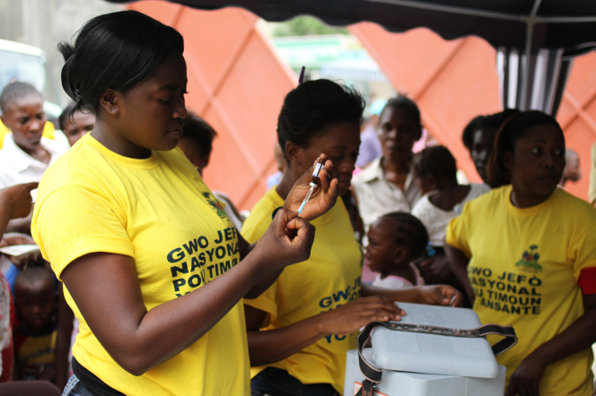 A Haitian woman in a yellow shirt holding a vaccine bottle upside down and filling a syringe while standing near other women.