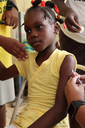 A young Haitian girl in a yellow shirt sitting down and receiving an immunization in her arm by a small syringe.