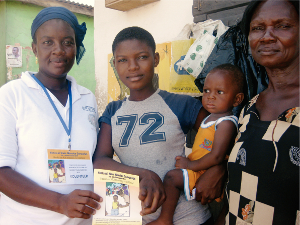 A woman in Africa holding a measles campaign flier and standing near another woman and a young woman holding a child.
