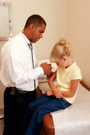 A doctor in a white shirt and black pants giving an injection in the arm of a young girl with blond curly hair sitting on a bed.