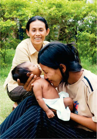 A smiling Cambodian mother sitting outside and holding her baby close to her face, with another woman nearby.
