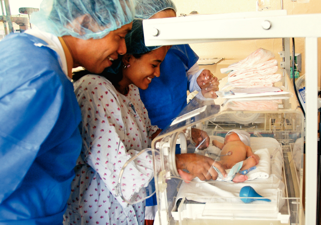 Two doctors in blue aprons looking at a baby as the mother reaches inside the baby incubator in a neonatal intensive care unit in the Dominican Republic.