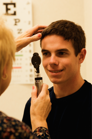A dark-haired young man in a black shirt having his eyes checked by a doctor with a long metal device.