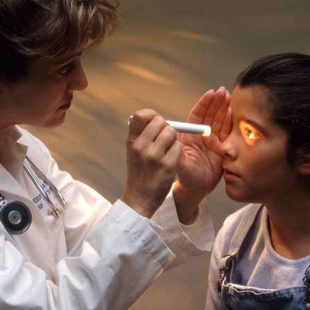A female doctor in a white coat shining a flashlight in the eye of a young girl.