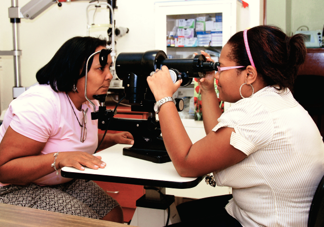 A Dominican woman in a light pink shirt sitting and resting her chin on an eye examination device while a doctor checks her eyesight.